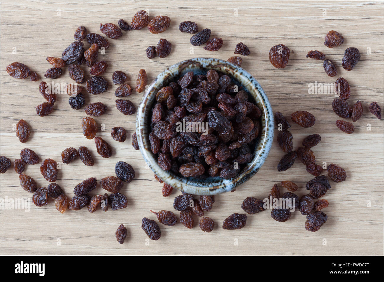 Organic raisins in handmade ceramic bowl on wooden table. Top view. - Stock Image