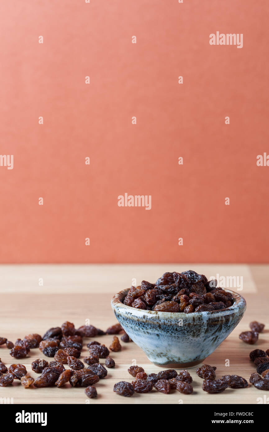 Organic raisins in handmade ceramic bowl on wooden table. Vertical image with copy space. Shallow depth of field. - Stock Image