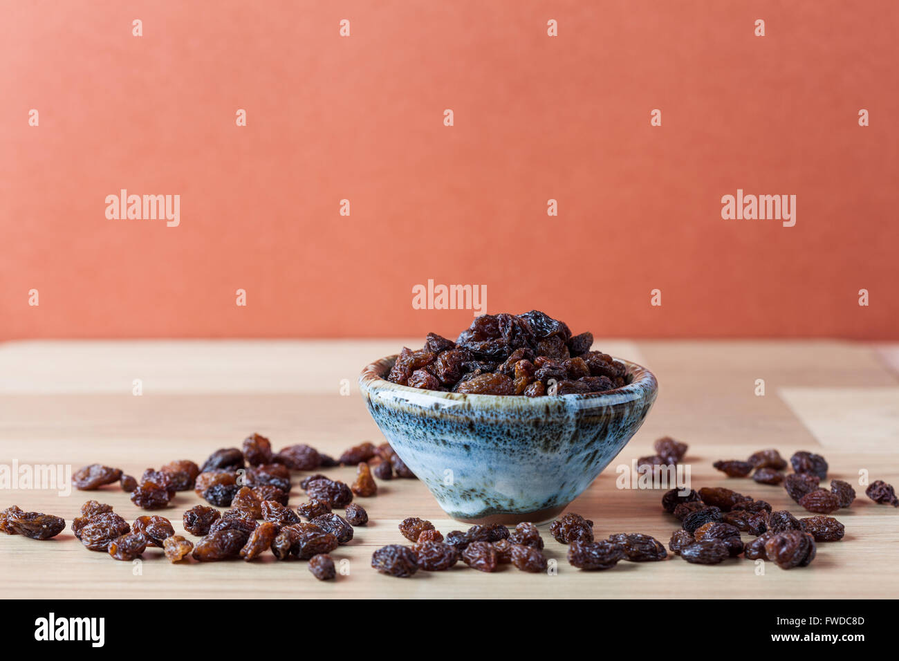 Organic raisins in handmade ceramic bowl on wooden table. Horizontal image with copy space. Shallow depth of field. - Stock Image