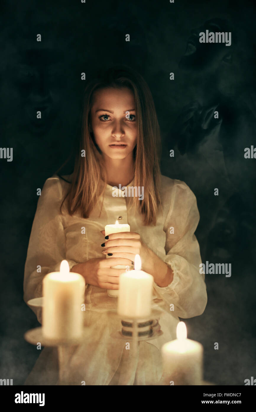 Young woman with candle lights surrounded by ghosts . Halloween and scary - Stock Image