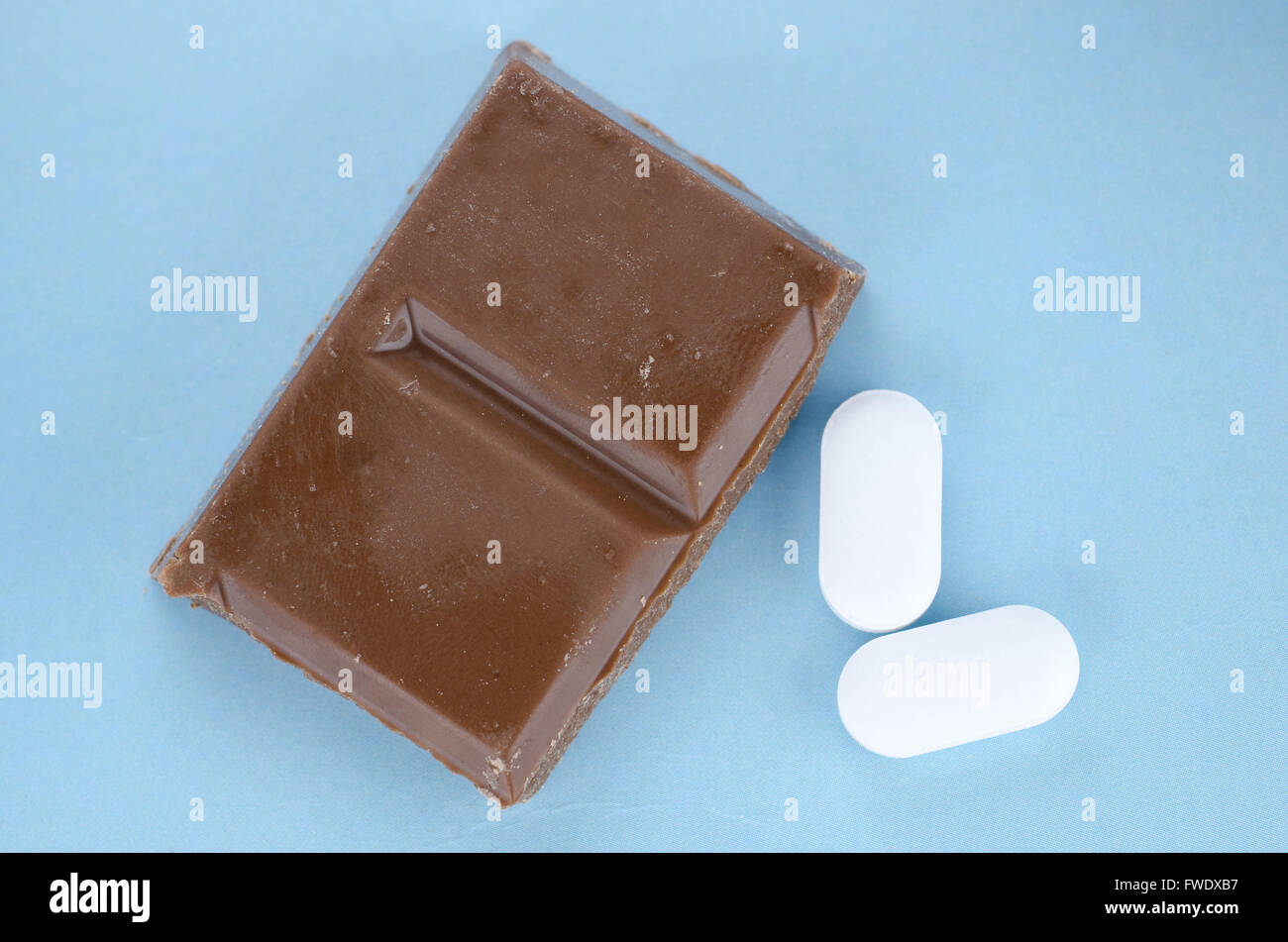 Chocolate triggers migraine headaches concept with piece of chocolate and two painkiller tablets - Stock Image