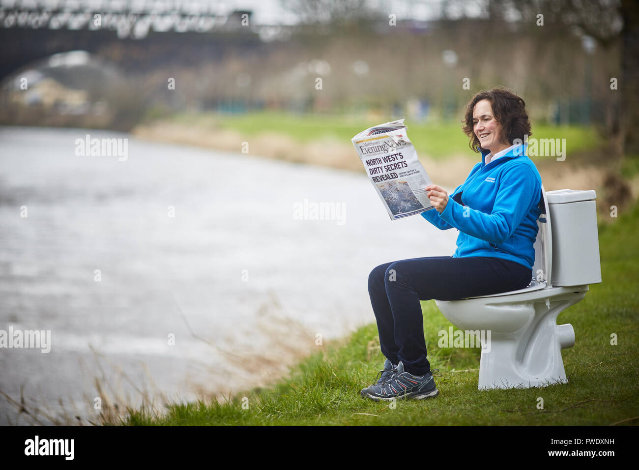 Sat on a toilet reading newspaper loo potty urinal sitting using sewage - Stock Image