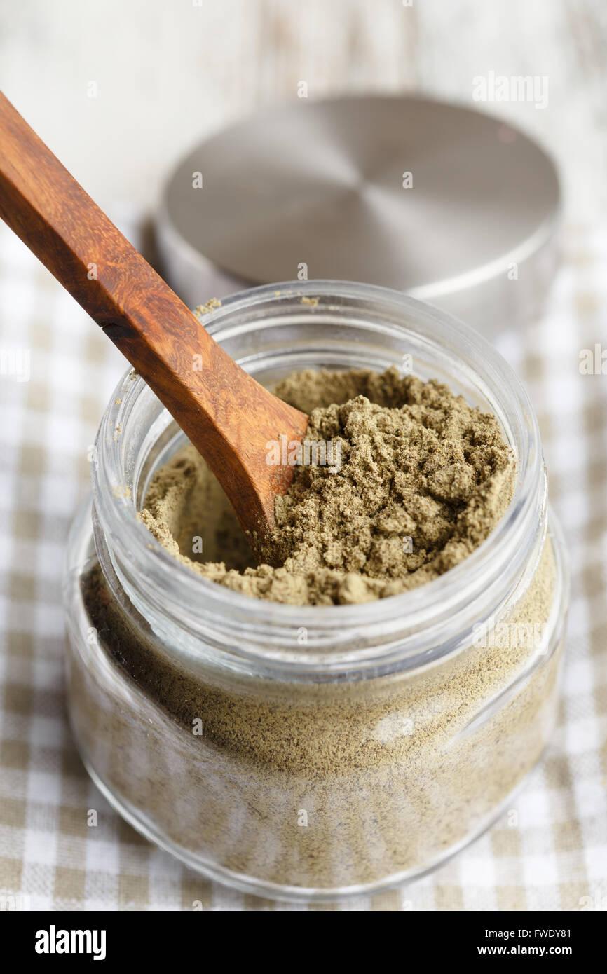 A glass jar of protein-rich hemp seed powder - Stock Image