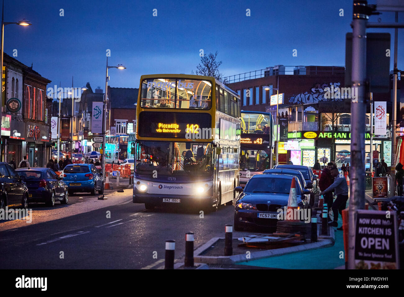 Rusholme curry mile willows road   Night dark evening 142 43 Stagecoach bus busy parked cars restaurants Restaurant - Stock Image