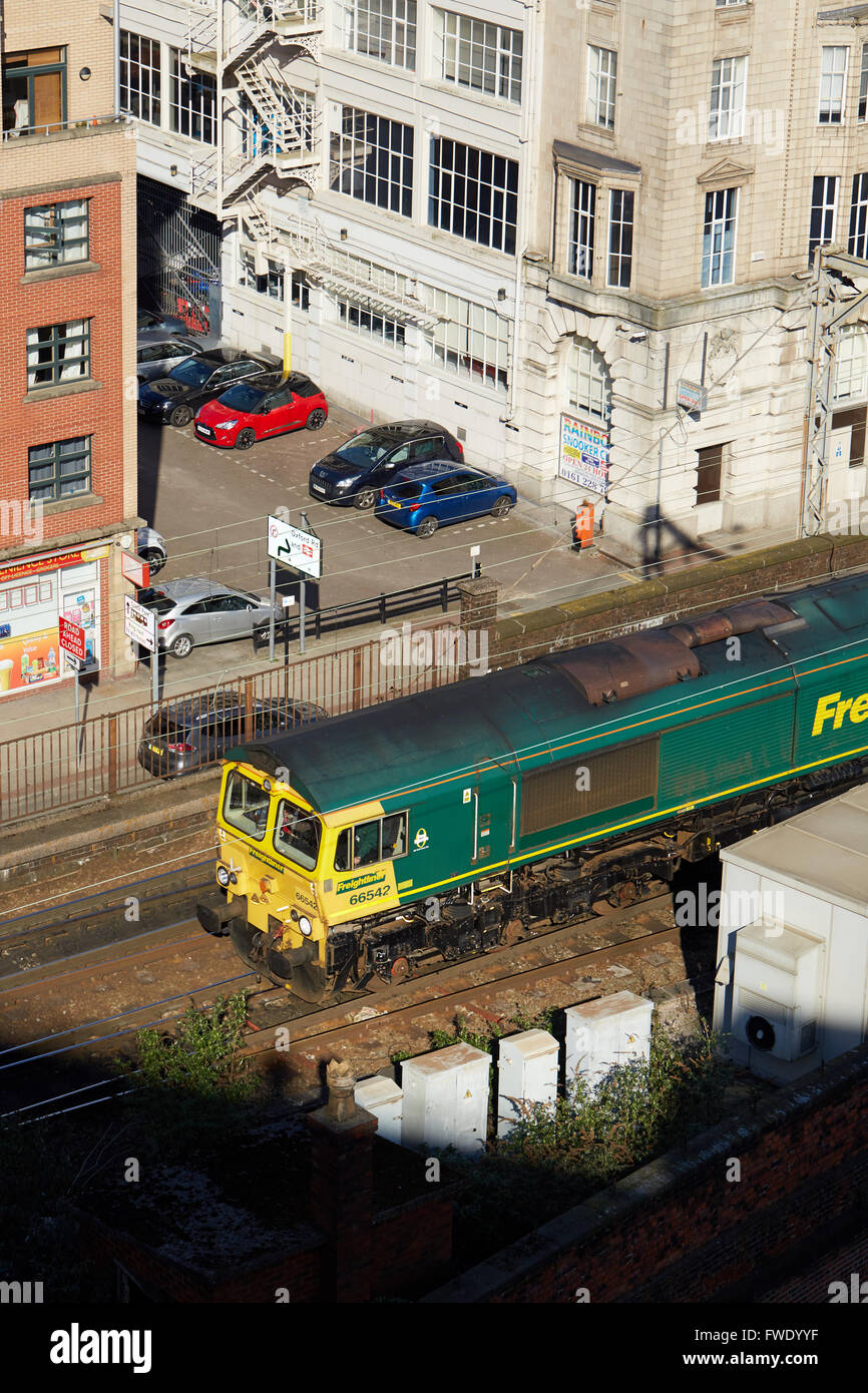 Manchester skyline oxford road railway station palace hotel   A class 66 freighliner locomotive making its way through - Stock Image