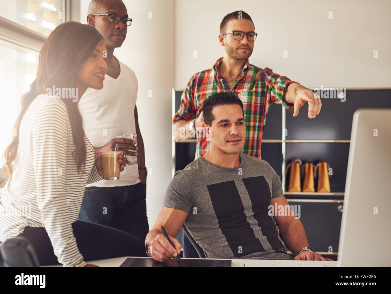Man in eyeglasses, beard and flannel shirt pointing at computer monitor in meeting with co-workers at office with - Stock Image