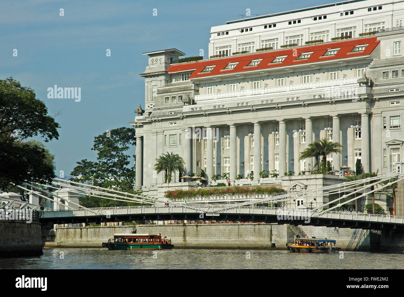The Fullerton Hotel and Cavenagh Bridge, from the Singapore River. - Stock Image