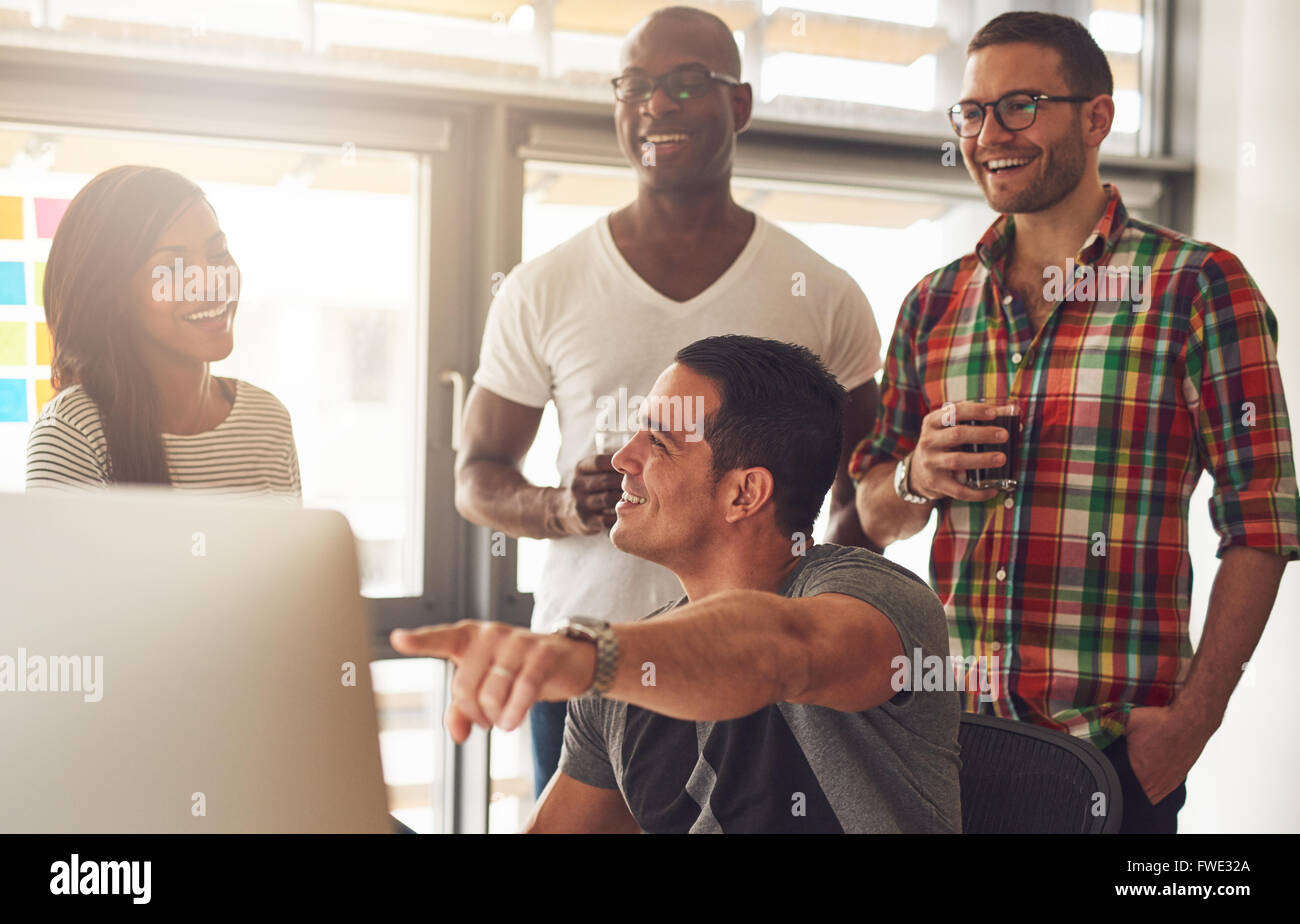Handsome young adult showing something on his computer to a group of three male and female casually dressed friends - Stock Image
