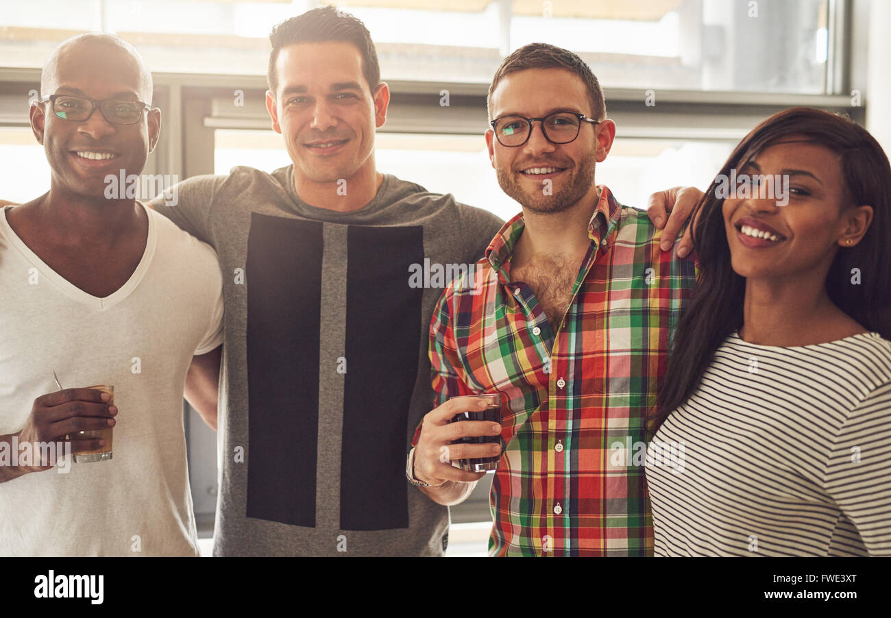Group of four Black, Caucasian and Hispanic happy adult friends wearing casual clothing and holding drinks while - Stock Image