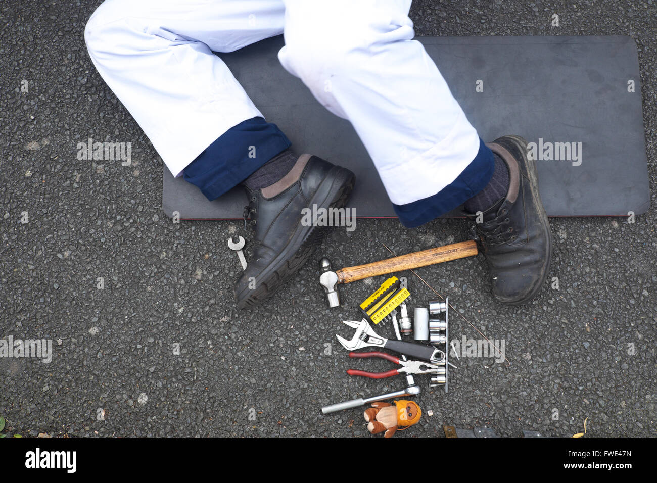 Car mechanic with his legs sticking out and tools at his feet - Stock Image