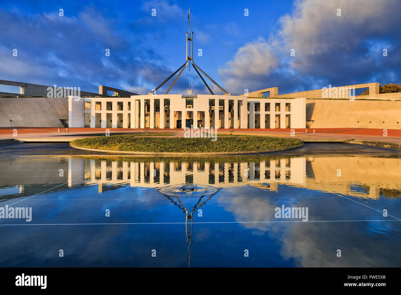 Facade of new Parliament house of Australia in Canberra with high flag on a flagpole with reflection in stil water - Stock Image