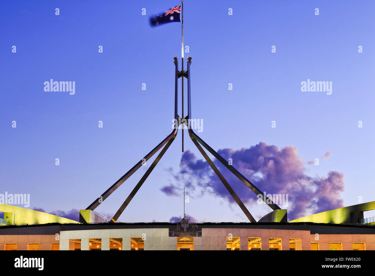 roof top part of Canberra parliament house - flagpole on four legs with flag and coat of arms at susnet with illumination. - Stock Image