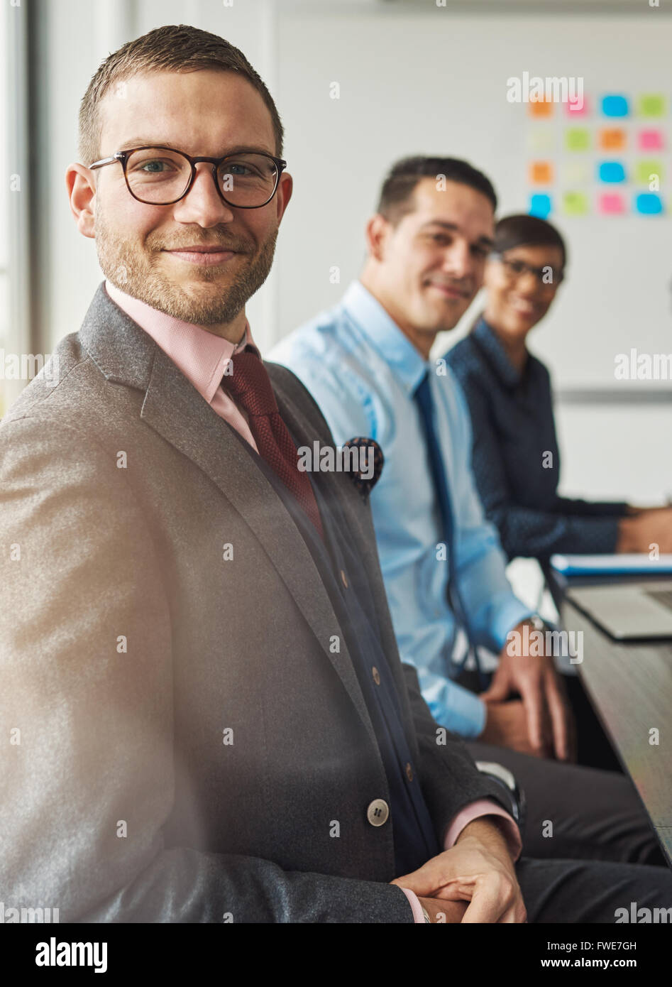 Handsome bearded man wearing suit and tie with two management colleagues in meeting at conference table in front - Stock Image
