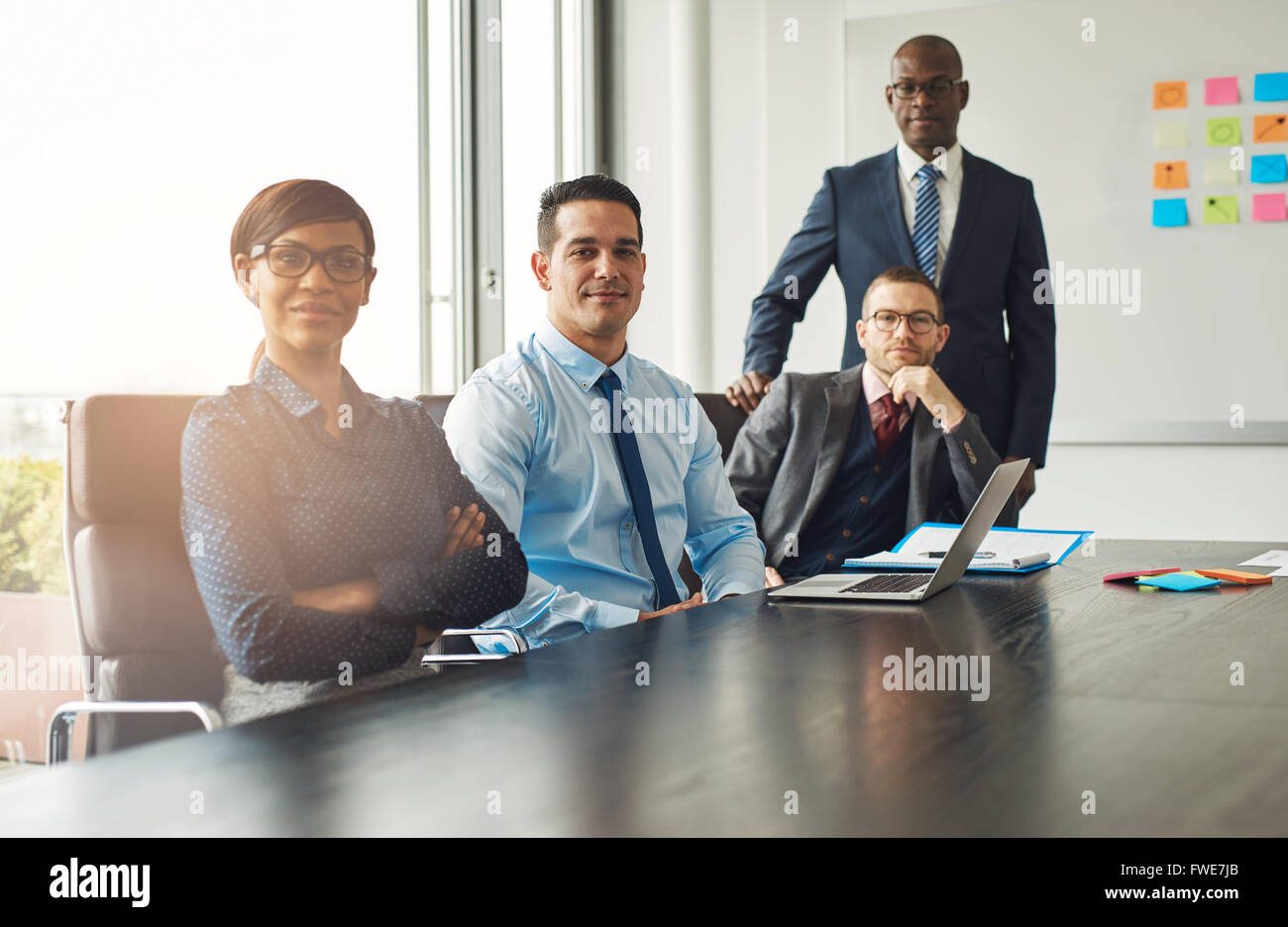 Four confident successful multiracial diverse business partners or associates seated at a boardroom table having - Stock Image