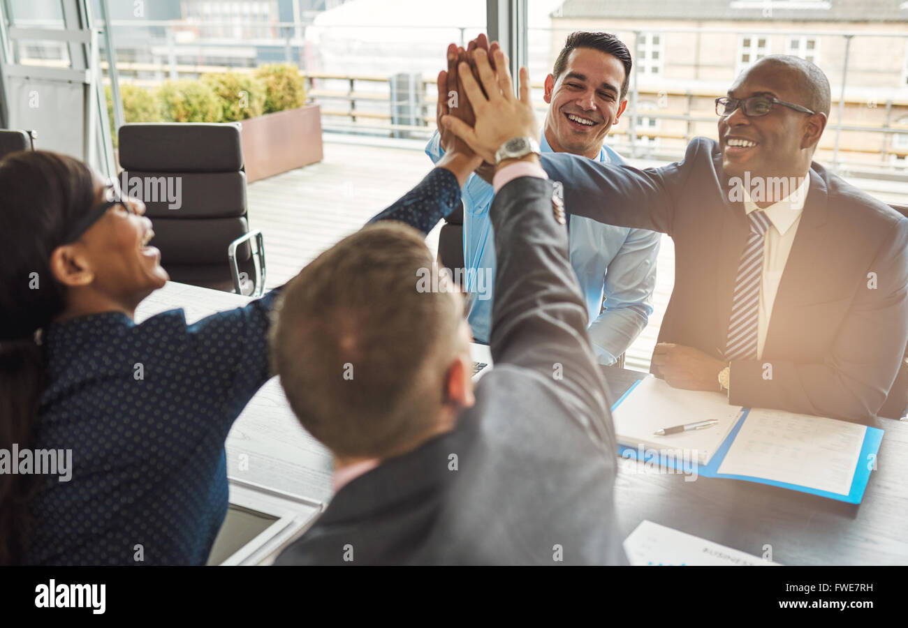 Exultant team of multiracial young business professionals rejoicing and congratulating each other giving a high Stock Photo