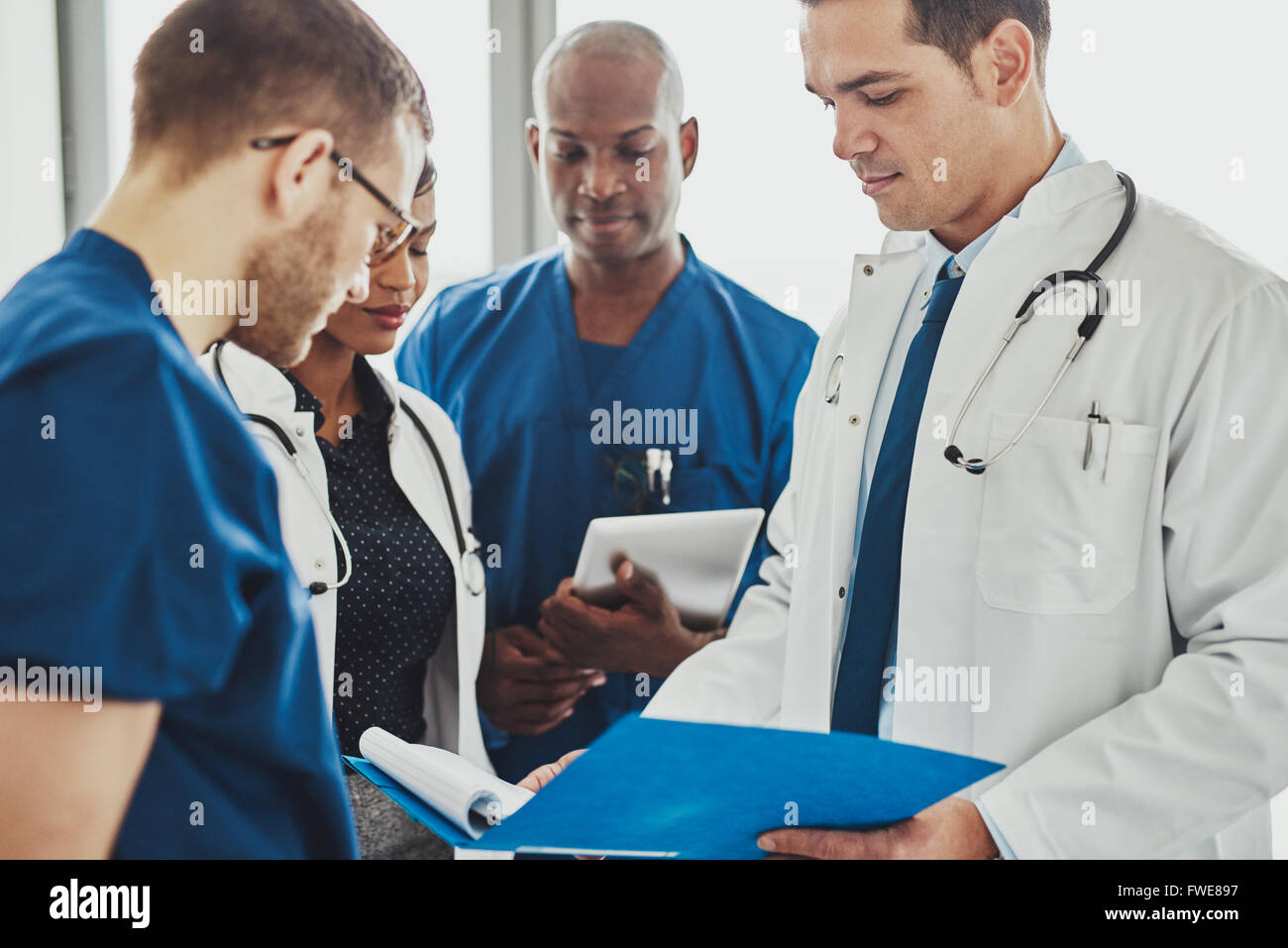 Doctors having a conversation looking at documents, mixed races, surgeons and doctors Stock Photo