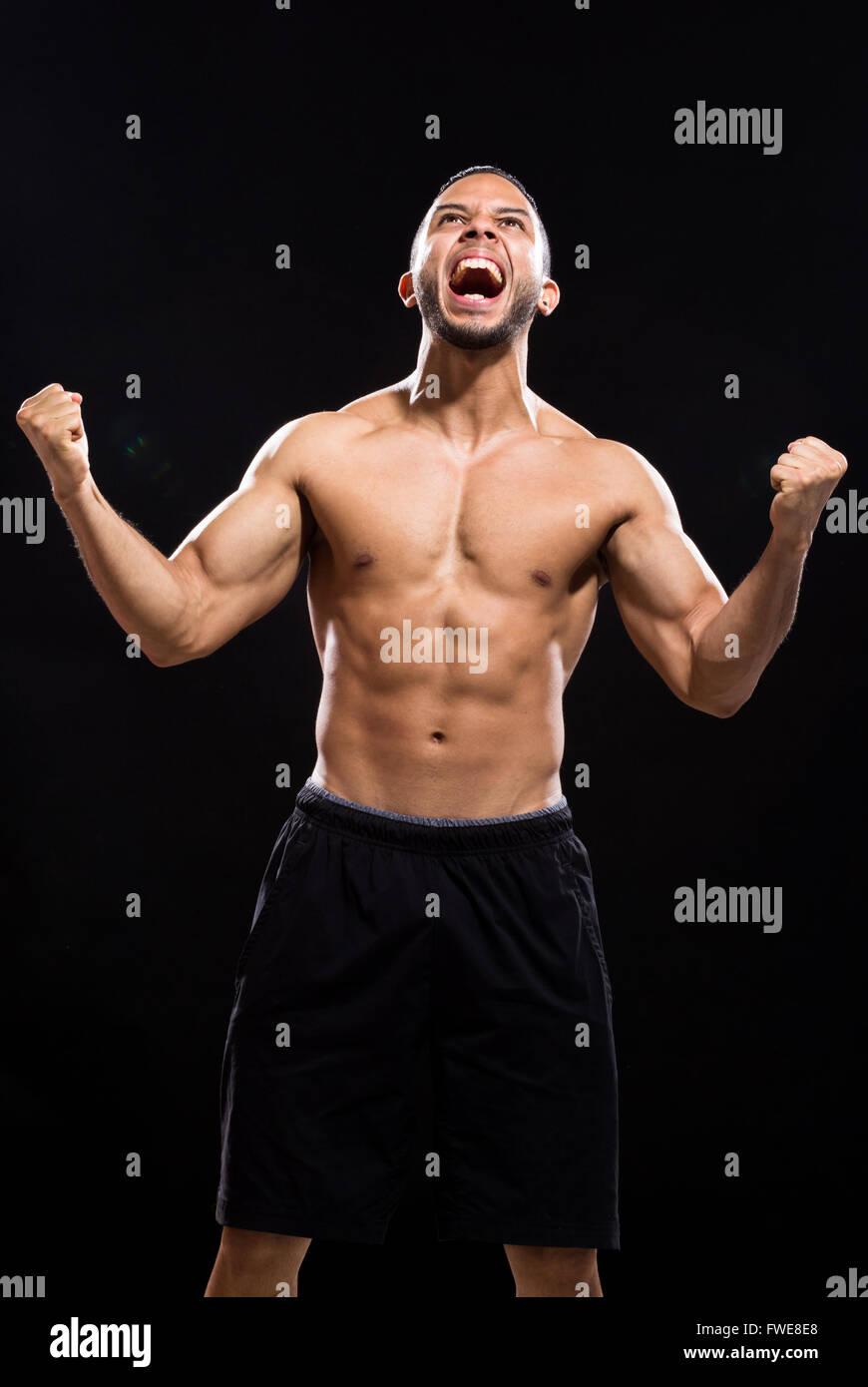 Furious man screaming. Black Background - Stock Image