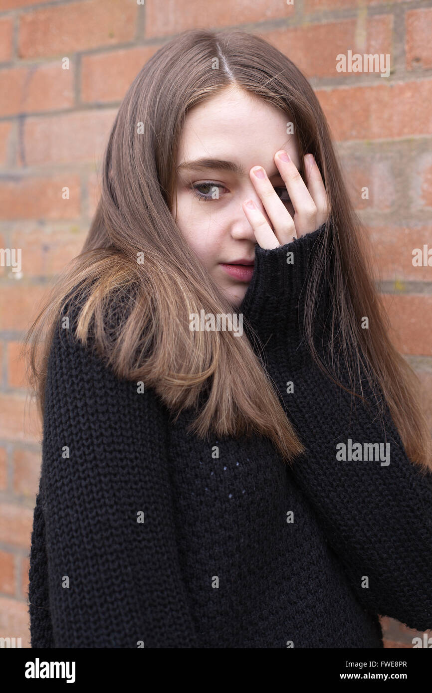 Young girl with her hand covering her face looking frightened - Stock Image