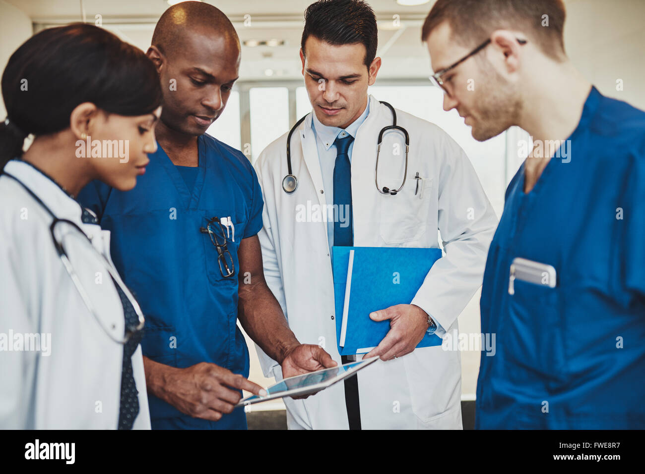 Team of multiracial doctors at hospital discussing a patient, Doctors using tablet - Stock Image