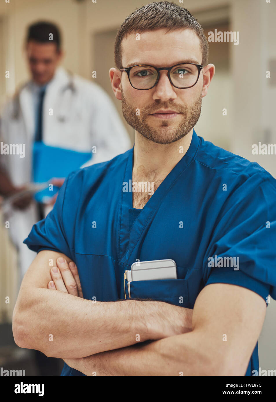 Serious confident young surgeon wearing glasses and surgical scrubs standing in a hospital with folded arms looking - Stock Image
