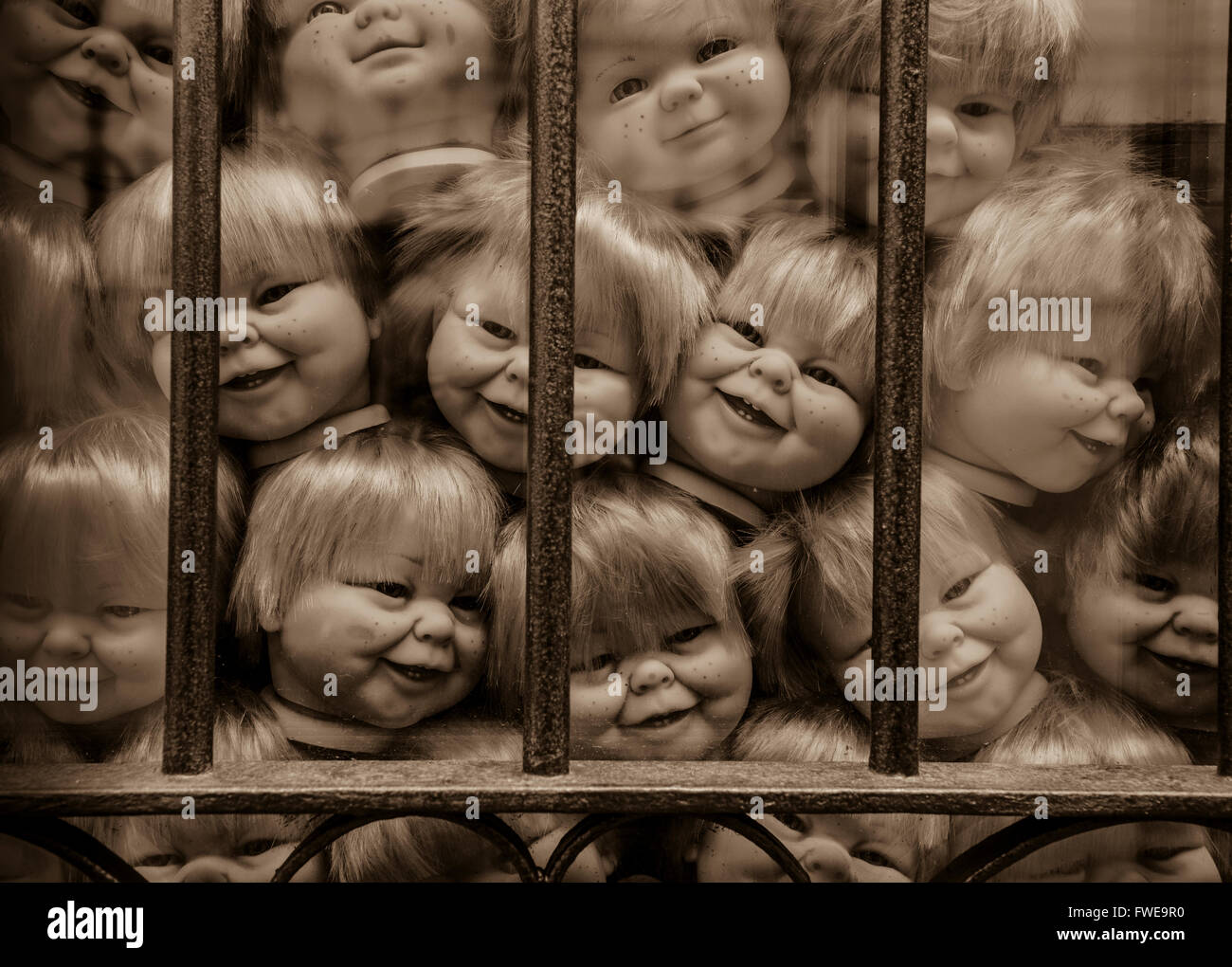 Creepy collection of baby doll heads in a window in Spain. - Stock Image