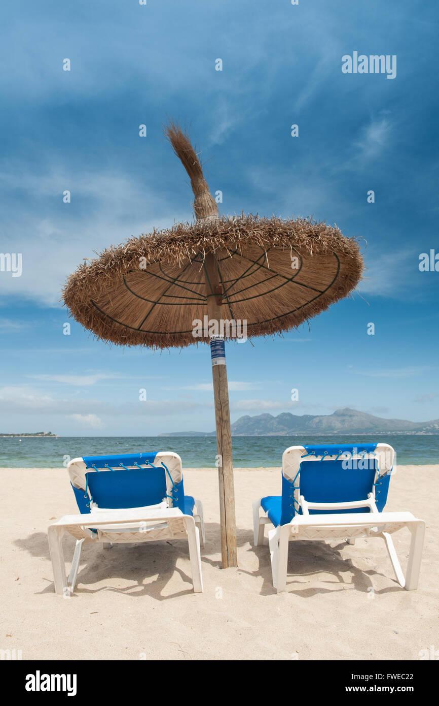 Beach Parasols and Sun Loungers on Pollenca Beach, Port de Pollenca, Mallorca, Balearics, Spain - Stock Image