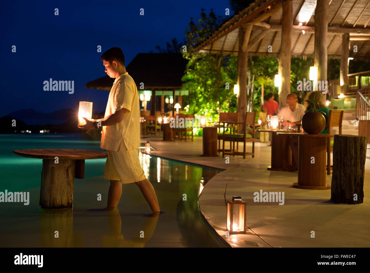 Six Senses Resort, Koh Yao Noi, Phang Nga Bay, Thailand, Asia. Waiter with a candles in the restaurant near the - Stock Image