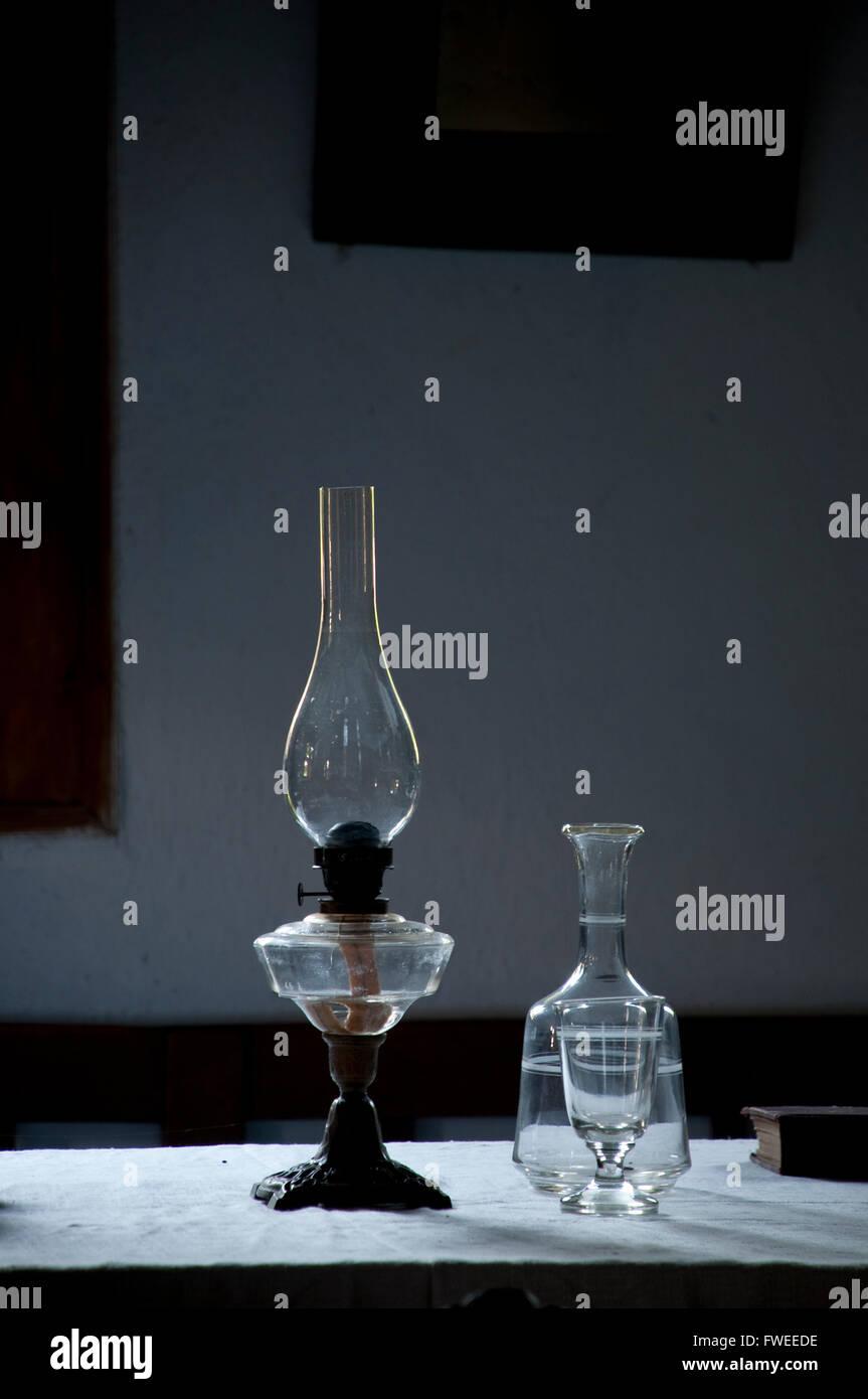 Kerosene lamp and bottle in traditional historic room - Stock Image