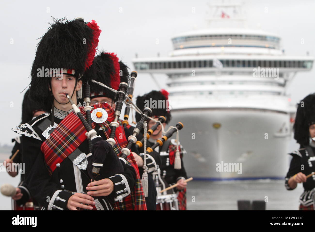 Pipers playing in front of cruise liner docking in Edinburgh - Stock Image