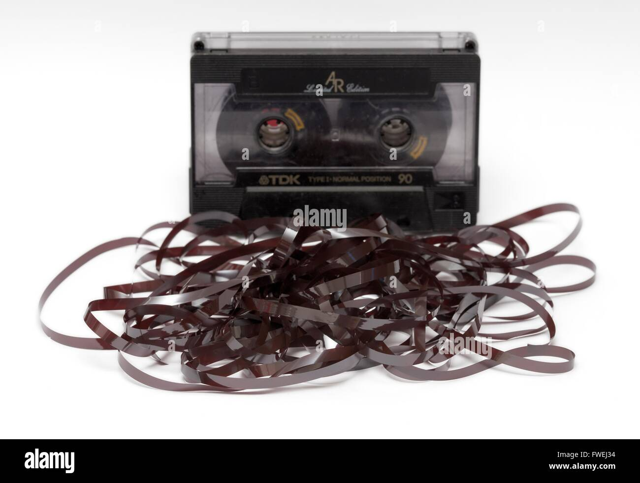 An audio cassette with magnetic tape pulled out. - Stock Image