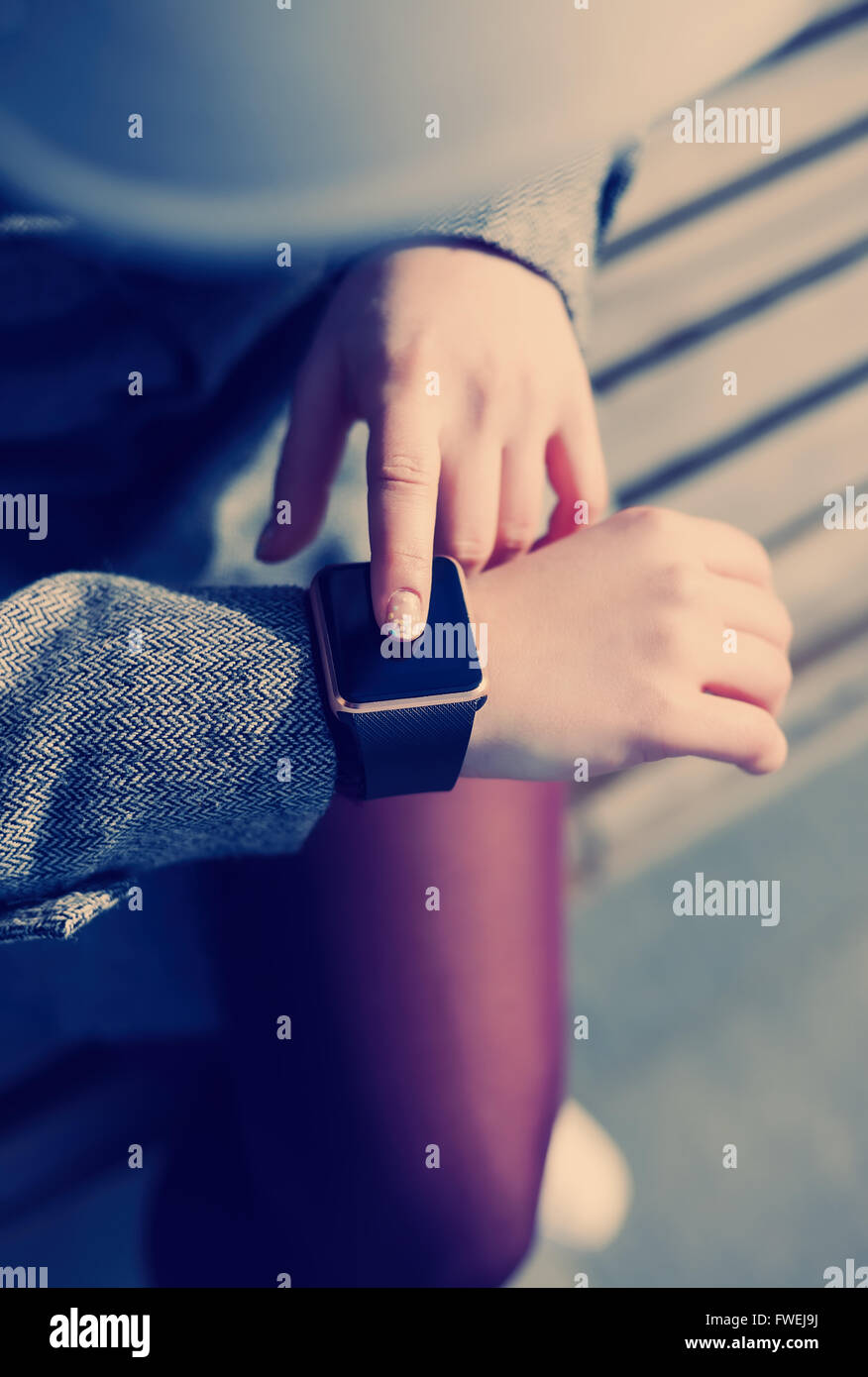 Female using her trendy smart wrist watch. This person is always connected to social media and internet. Modern - Stock Image