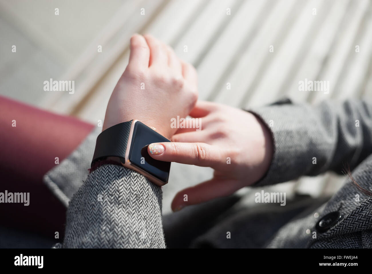 Female using her trendy smart wrist watch sitting on the bench. This person is always connected to social media - Stock Image