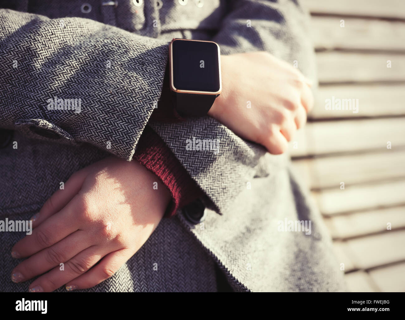 Woman in grey coat wearing stylish black smart wrist watch. This person is always connected to social media and - Stock Image