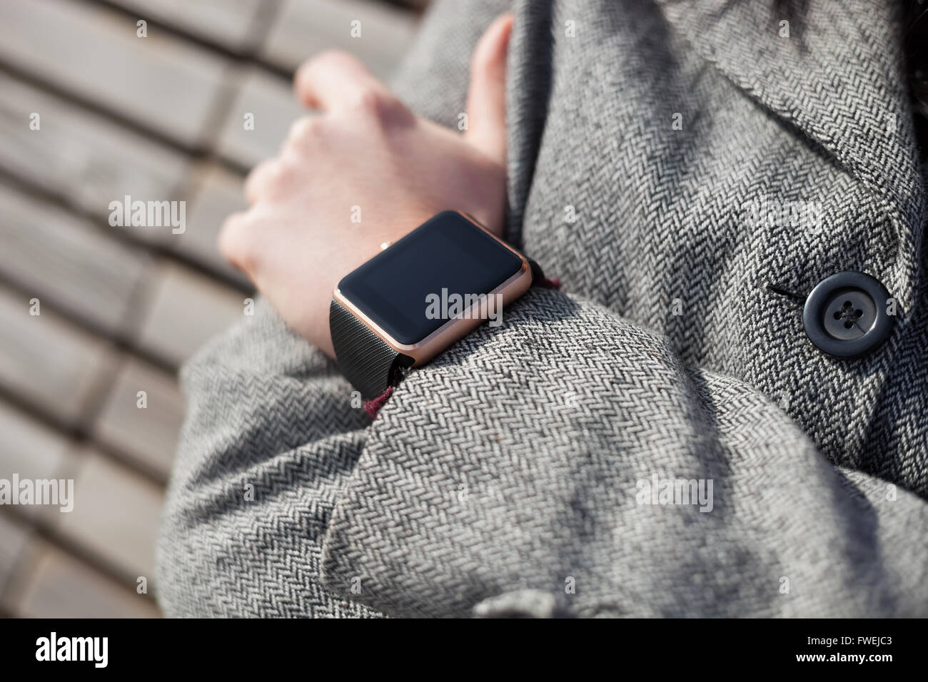 Woman in grey coat wearing modern smart wrist watch. This person is always connected to social media and internet - Stock Image