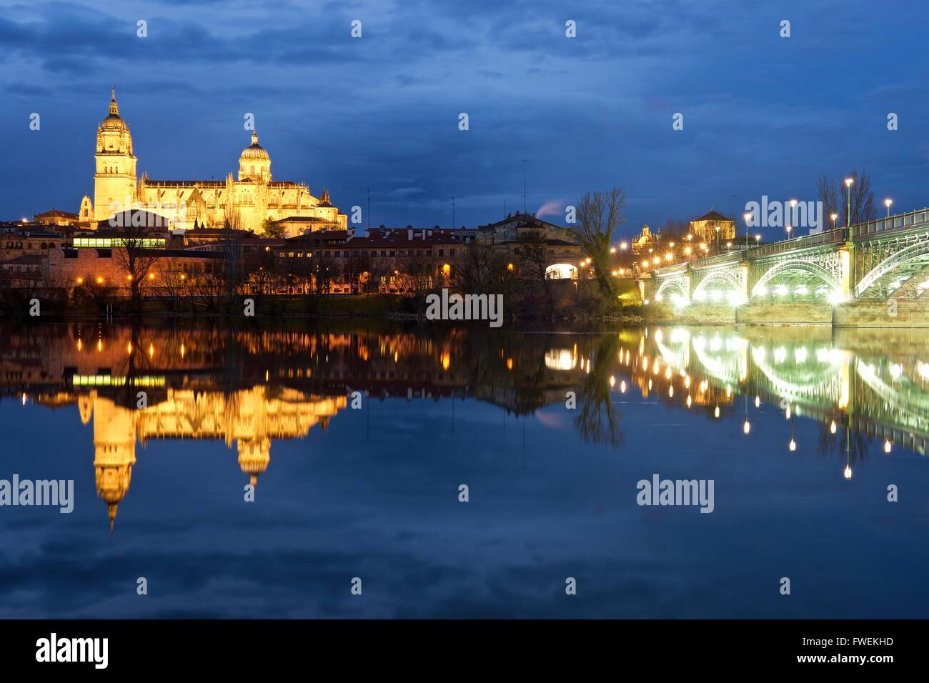 Salamanca Cathedral and still water reflections of it lit up at night - Stock Image