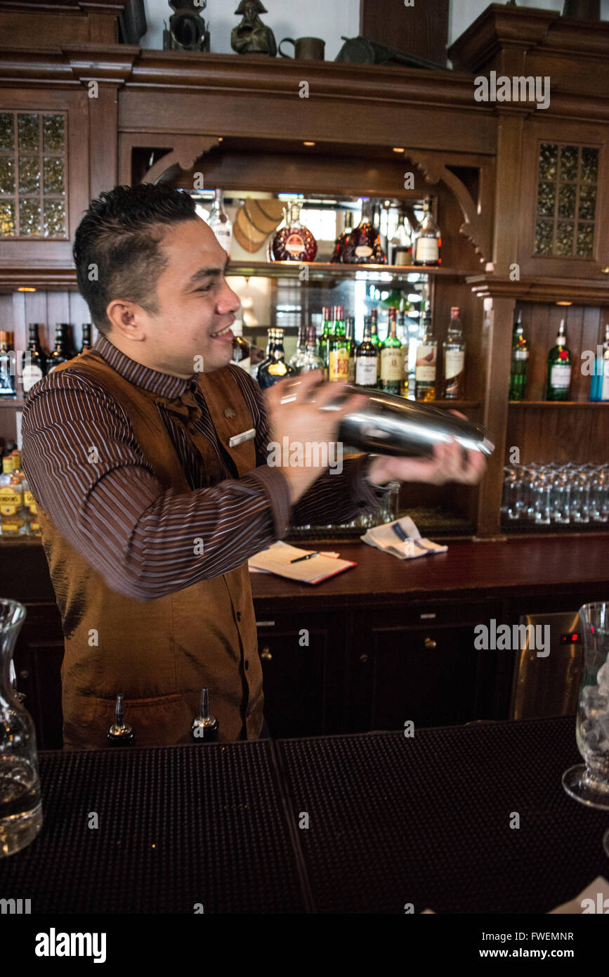 A barman making the famous cocktail drink ,'Singapore Sling' in the Long Bar at the Raffles Hotel in Singapore. - Stock Image