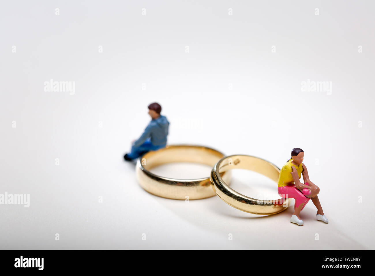Concept image of a couple sat on wedding rings to illustrate divorce and separation - Stock Image