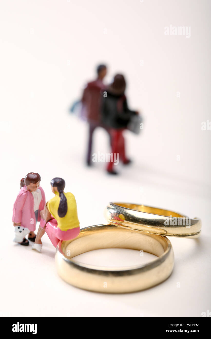 Concept image of a woman sat on wedding rings talking to a child to illustrate divorce the effects on children - Stock Image