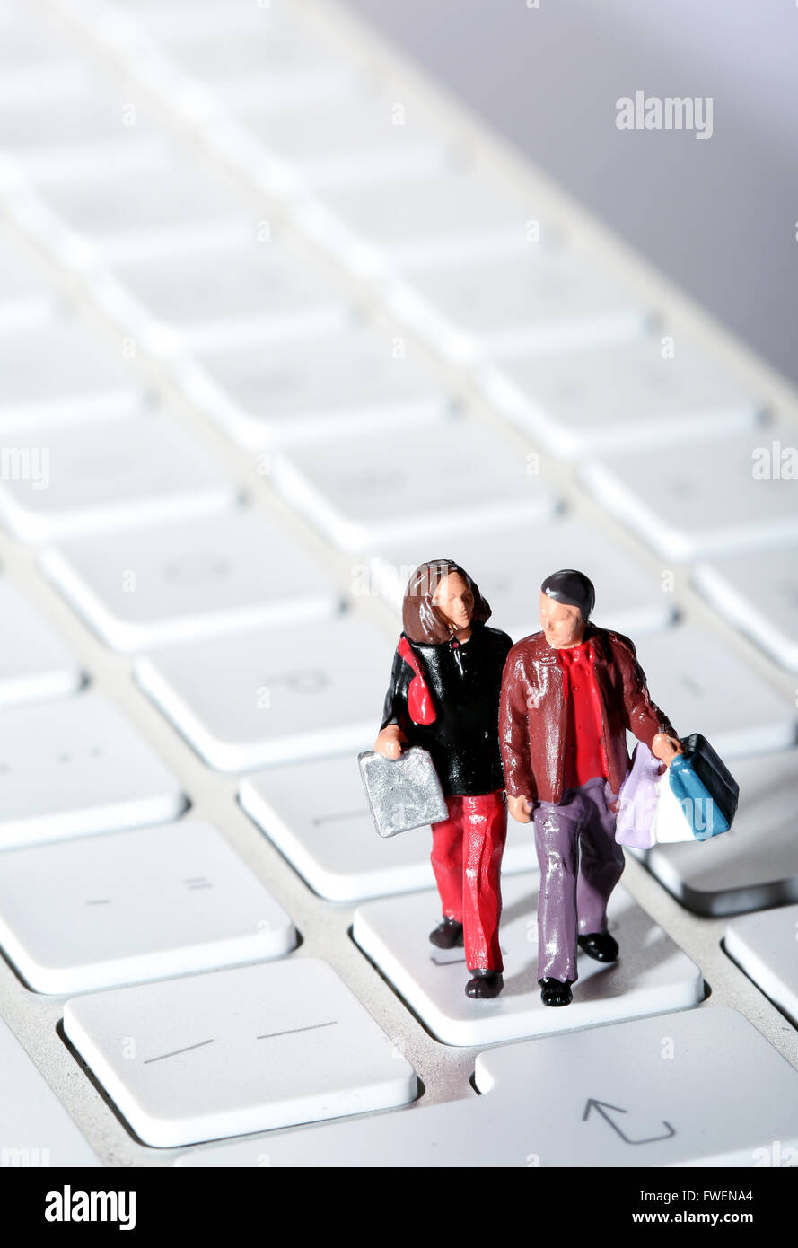 Online Shopping concept image of a couple on a computer keyboard carrying shopping bags - Stock Image