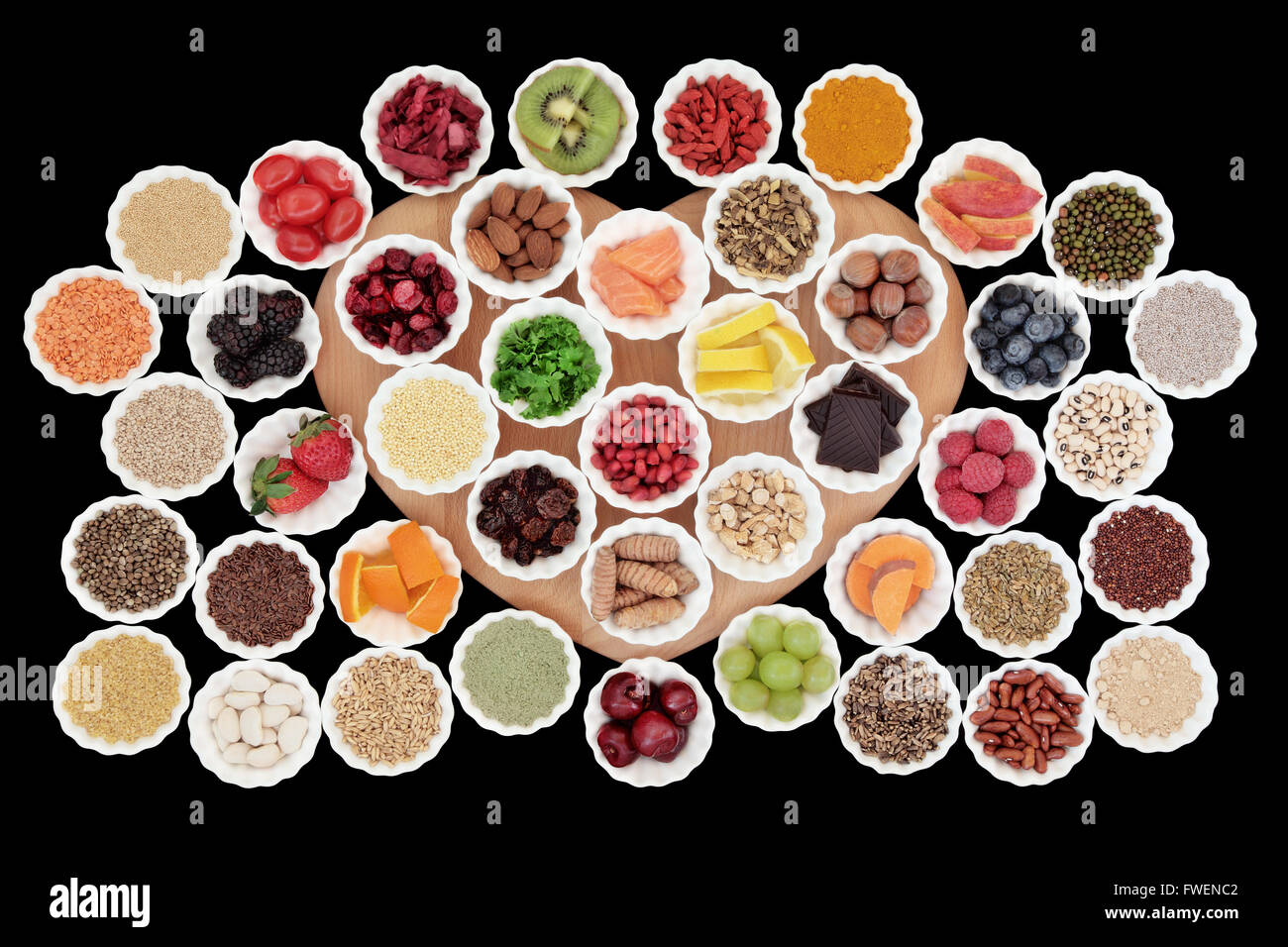 Health and diet super food selection in porcelain crinkle bowls on a heart shaped board. High in vitamins and antioxidants. - Stock Image