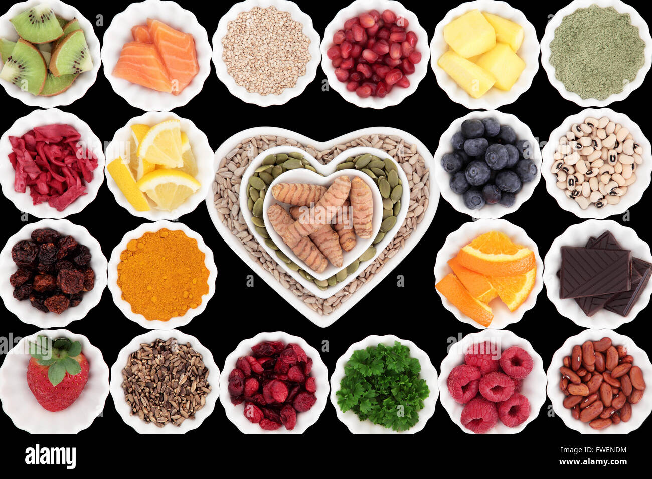 Health and super food selection in porcelain crinkle bowls over black background. High in vitamins and antioxidants. - Stock Image