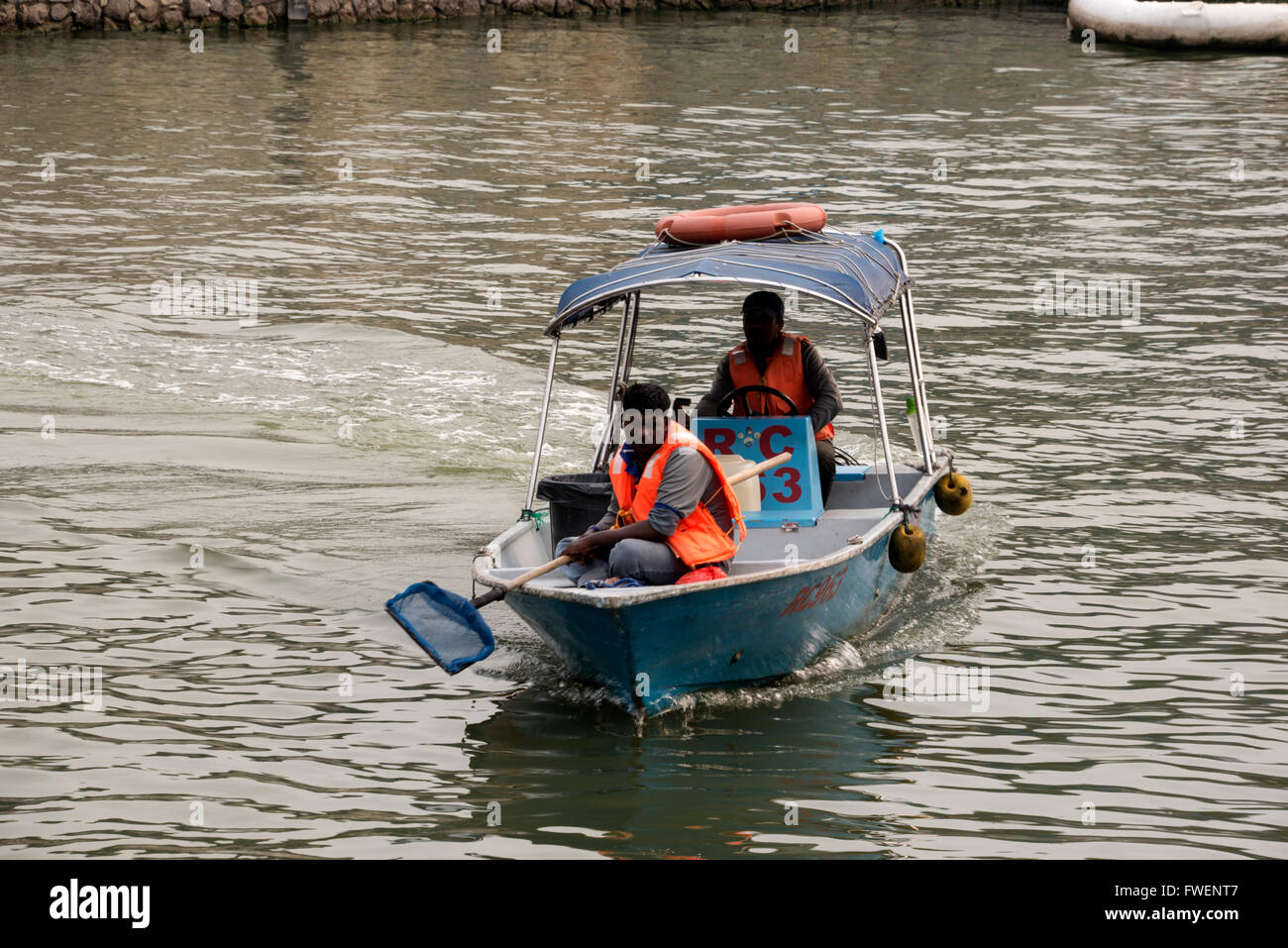 A boat crew cleaning up dumpted rubbish and floating objects on the Singapore river in Singapore - Stock Image