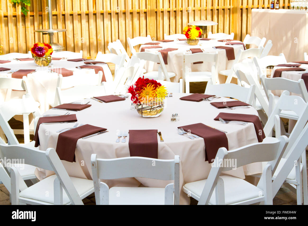 Place settings tables and chairs are empty before the guests arrive at a wedding reception. & Place settings tables and chairs are empty before the guests ...