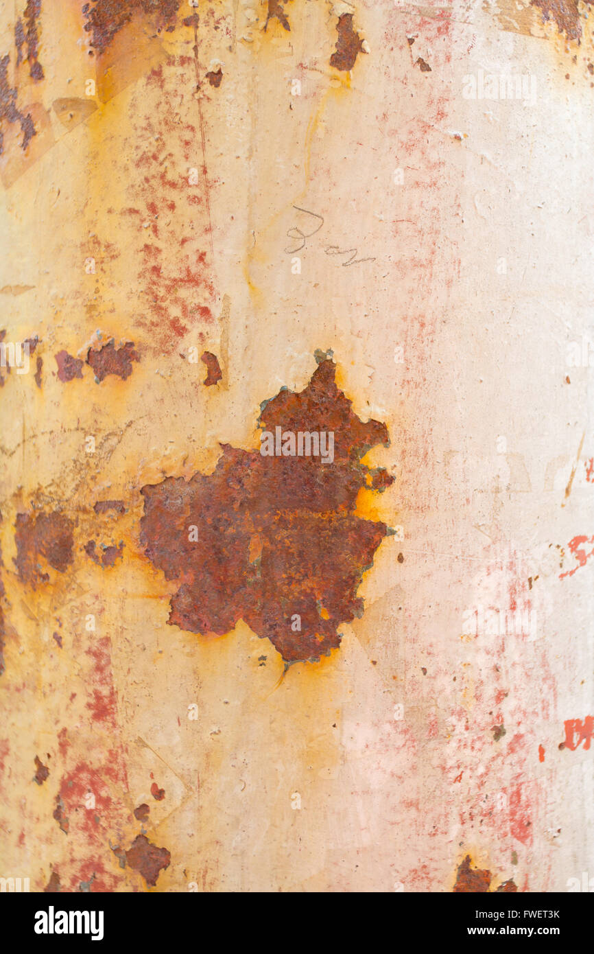 Paint peels off this rusty weathered pole showing some muted tones of white pink orange and red. - Stock Image