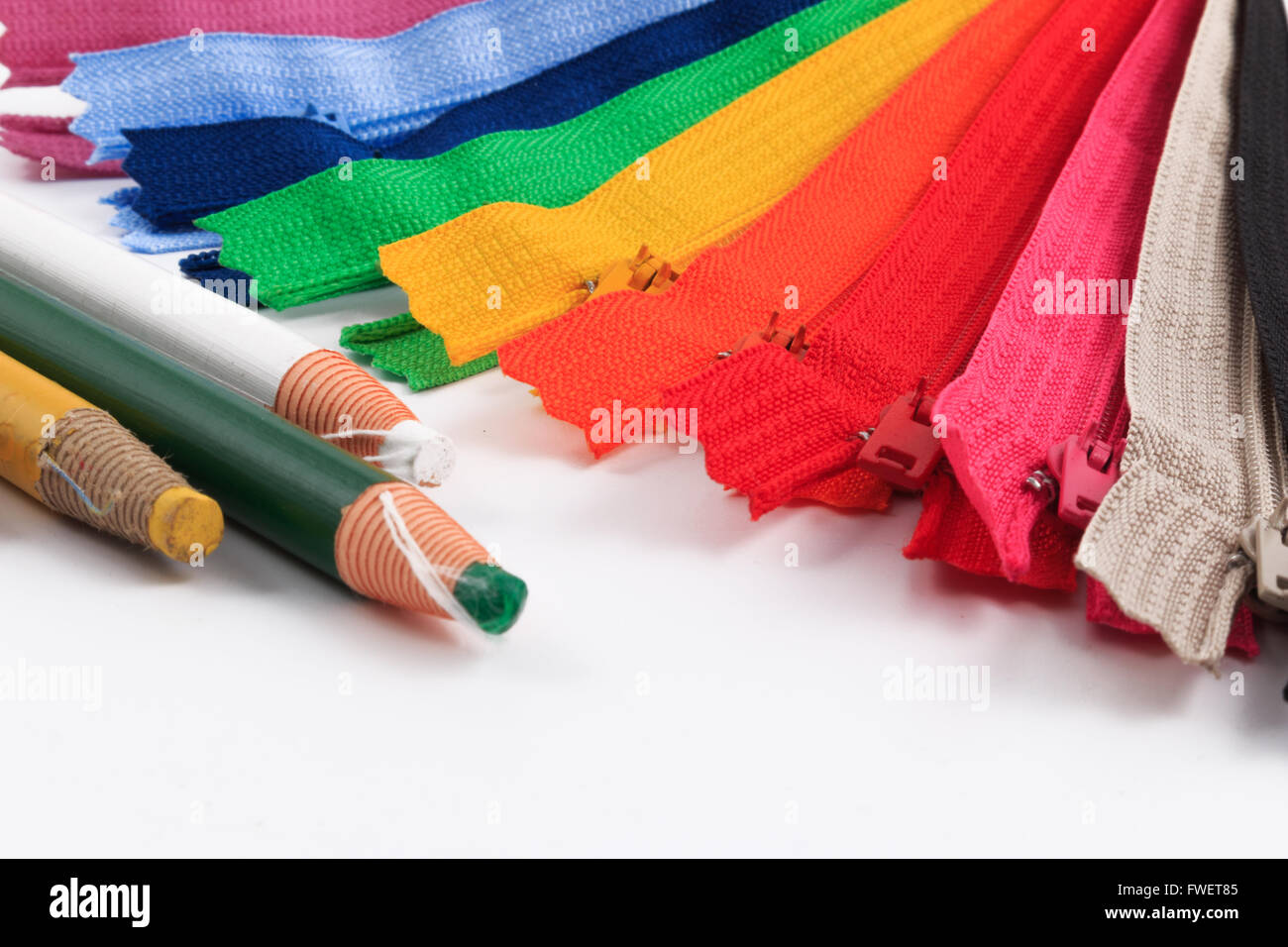 Colorful zippers and pencils white background. - Stock Image