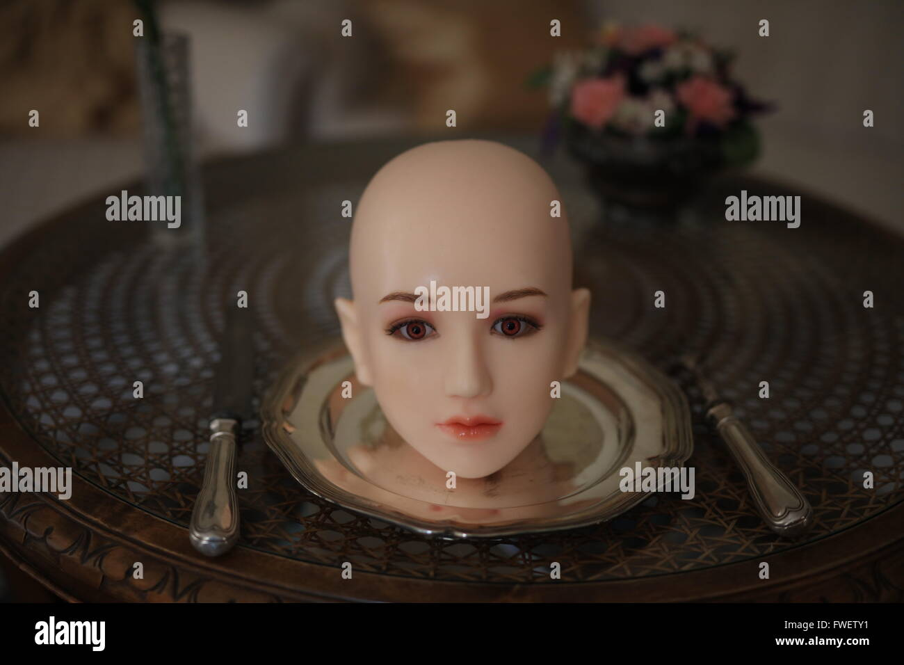 Bald head on a silver plate with cutlery - Stock Image