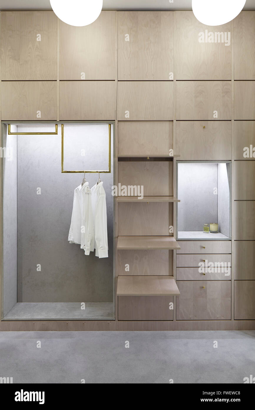 Concealed wardrobe door in the changing area with shirts hanging. Selfridges  Manchester, Manchester, United Kingdom. - Stock Image