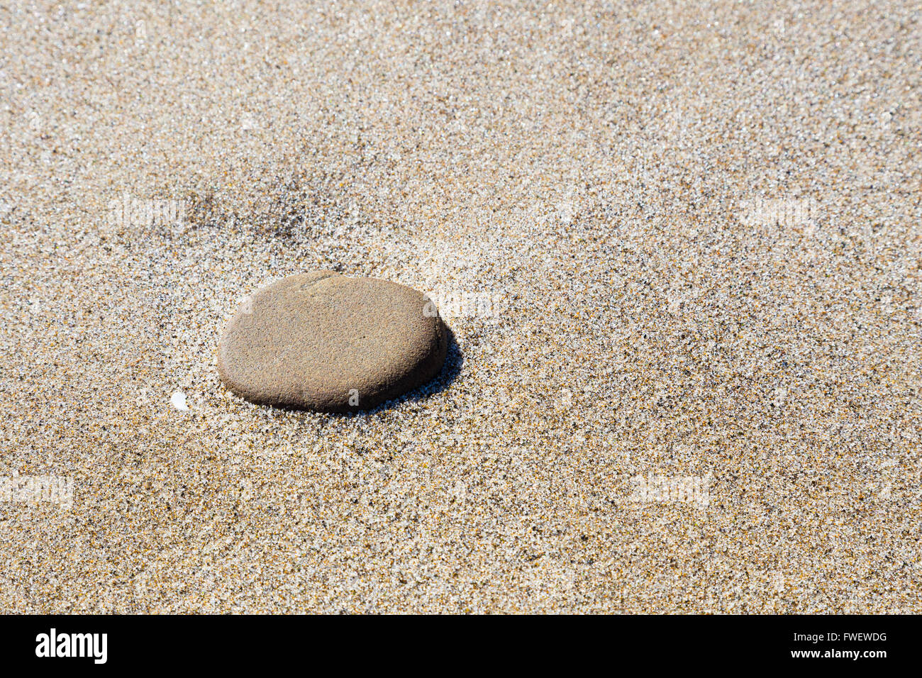 A large stone sits on some fine sand at the beach in Oregon along the coast. - Stock Image
