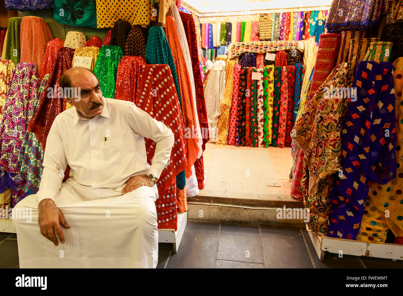 Shopkeeper seated outside his shop surrounded by  colourful material, Souq Waqif, Doha, Qatar, Middle East - Stock Image