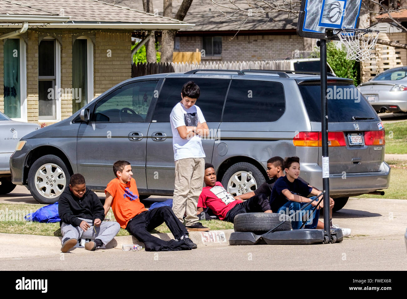 Six preteen boys take a break from playing basketball and sit on a neighborhood curb together in Oklahoma City, - Stock Image
